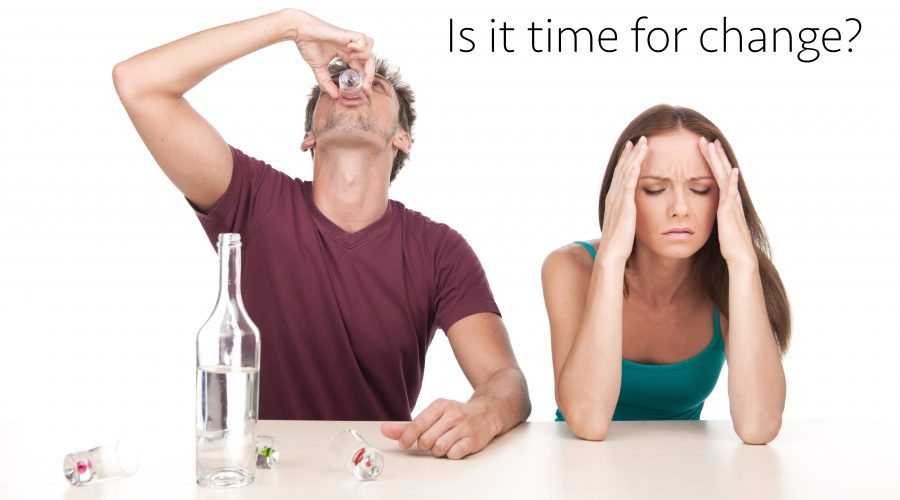 Man drinking alcohol and woman sitting upset at table. Photo of woman with alcoholic husband on white background