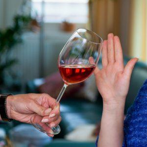 Eine junge Frau mit Autoschlüssel verweigert ein Glas Wein. Don't drink and drive